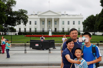A family poses for a photograph using a selfie stick outside the White House in Washington