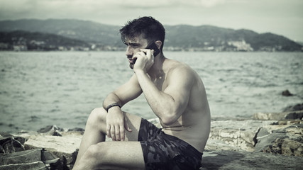 Athletic man at the seaside using cell phone to call someone with the sea behind him