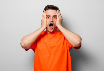Young handsome man in orange t-shirt. Studio image on white background