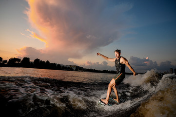 Active man riding on wakesurf down the river