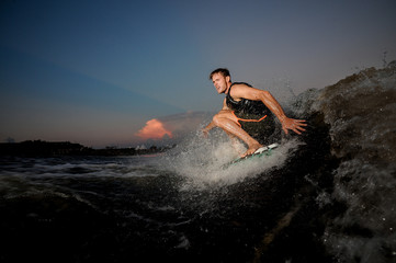 Young and active man riding on wakesurf down the river during summer sunset