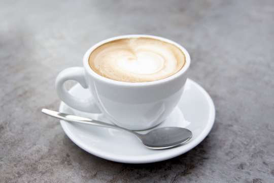Nice white cup of hot cappuccino coffee with cream milk foam and spoon.jpg