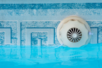 Closeup of an overflow outlet mechanism nozzle set in a swimming pool with water. Copy space.