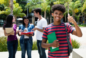 African male student showing thumb with group of other international students