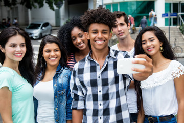 Large group of international young adults taking selfie with phone outdoor in the summer