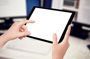 Female hands holding and touching empty screen of black tablet in horizontal position, blurred office desk with computer in background. Mockup