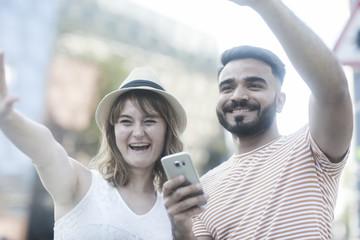 Junges Paar mit Smart Phone winkend