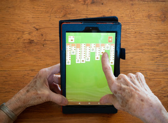 Close Up of an Elderly Woman's Hands Playing Solitaire on a Tablet