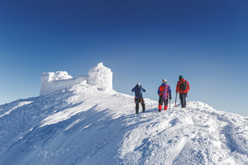 Three brave rescuers explore the terrain of snowy slope for avalanche danger against snow capped old observatory at peak of Carpathian mountain. Rear view. Winter seasonal landscape.