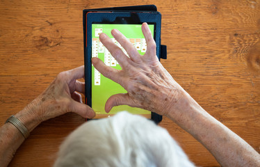 Elderly Woman Making a Solitaire Move on a Tablet