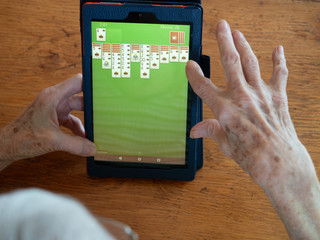 Elderly Woman Playing Solitaire on a Tablet with a Green Screen. Her hands and a portion of her head are shown.