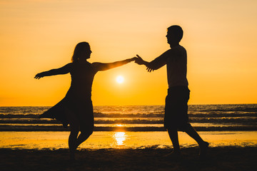 Beautiful silhouettes of dancers at sunset