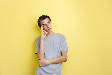 Pensive handsome young thin dark-haired guy with blue eyes wearing gray t-shirt standing against yellow background