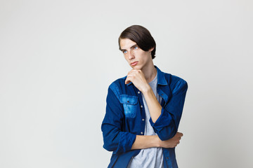 Thoughtful handsome young thin dark-haired guy with blue eyes wearing blue denim shirt, holding hand on chin, standing against white background