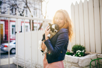 A young red-haired Caucasian woman holds a small funny dog in the arms of two colors of black and white chihuahua. Hugs and kisses love shows against a white wooden fence at sunset
