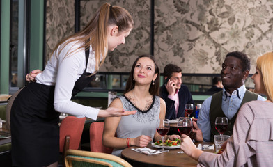 Positive company talking with waitress in restaurant