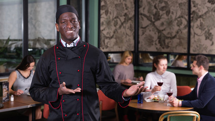 Smiling politely African American chef inviting to visit cozy restaurant