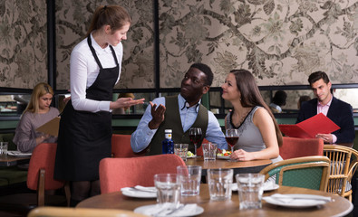 Waitress talking with satisfied couple in restaurant
