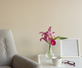 Close up of retro grey armchair next to small white side table with bright pink flowers, blank square picture frame, cup and glasses (selective focus)