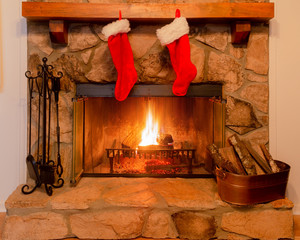 Two Christmas stockings on the mantle of a stone fireplace with a warm fire.