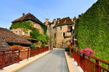 Wall Mural - Flower lined bridge in the beautiful Dordogne village of Carennac, France
