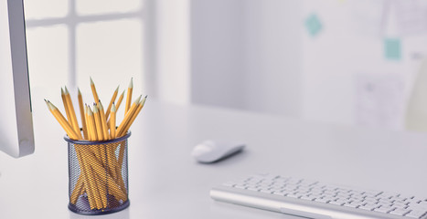 Graphite pencils in a metal grid-container on the office table.