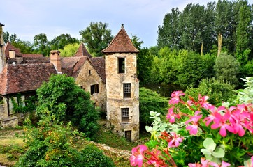 Fototapete - Old medieval house and tower with flowers in the quaint village of Carennac, France