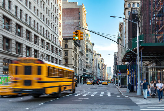 Yellow bus blurred in motion driving fast down Fifth Avenue in Manhattan New York City NYC