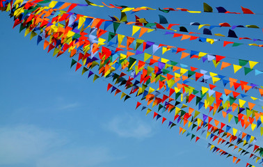 Multicolored triangular small flags to celebration party against blue sky.Street holiday concept with space for text.Selective focus.