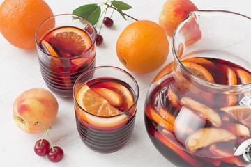 Refreshing red wine sangria summer drink / Refreshing red wine sangria summer drink in glasses with orange fruit and peach on white wooden background