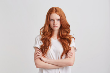 Portrait of confident attractive redhead young woman with long wavy hair and freckles wears t shirt looks serious and keeps arms crossed isolated over white background