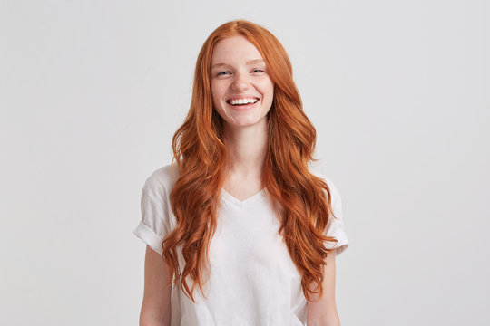 Portrait of cheerful cute redhead young woman with long wavy hair and freckles wears stylish t shirt looks relaxed and laughing isolated over white background Feels happy