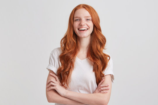 Portrait of cheerful pretty redhead young woman with long wavy hair and freckles wears t shirt keeps hands folded and laughing isolated over white background