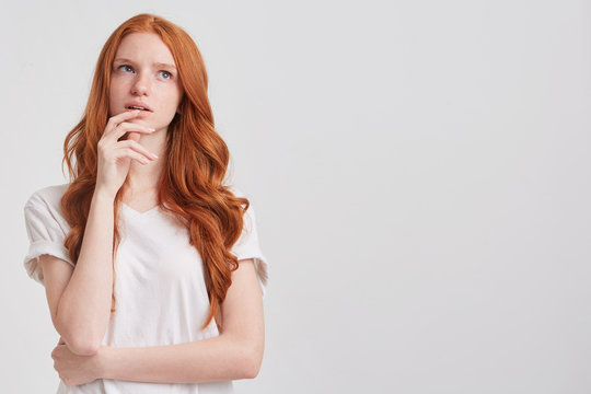Portrait of pensive attractive redhead young woman with long wavy hair and freckles wears t shirt touching her chin and thinking about future isolated over white background