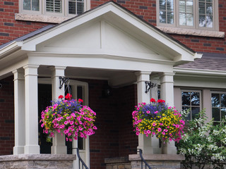 covered front porch with hanging baskets of flowers