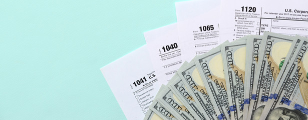 Tax forms lies near hundred dollar bills and blue pen on a light blue background. Income tax return