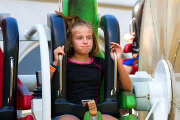 PreTeen Girl Looks Either Bored or Naseous on a Fast Spinning Ride at an Amusement Park