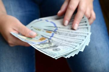 A girl holding a fan of dollar bills