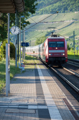 Red train entering train station with focus on platform clock