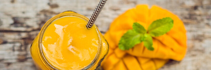 Mango smoothie in a glass Mason jar and mango on a green background. Mango shake. Tropical fruit concept BANNER, long format