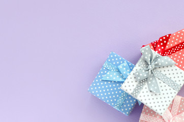 Pile of a small colored gift boxes with ribbons lies on a violet background. Minimalism flat lay top view