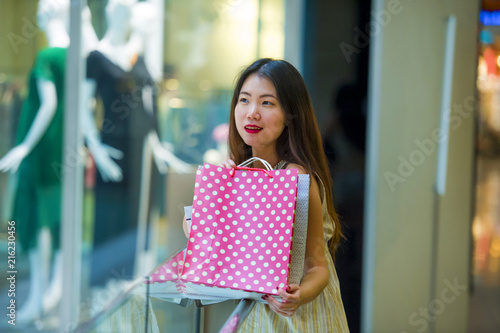 3a8c8938880 lifestyle indoors portrait of young happy and beautiful Asian Korean woman  carrying shopping bags in mall