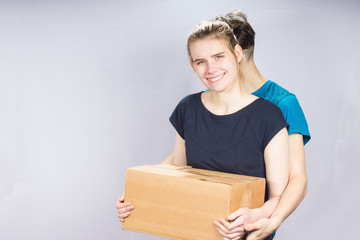 the girl tenderly embraces her friend holding a box