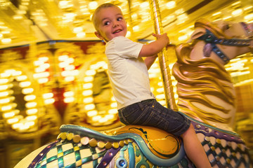 Cute little boy having fun riding a carousel at an amusement park or carnival. Happy little boy riding a merry go round carousel with bright lights