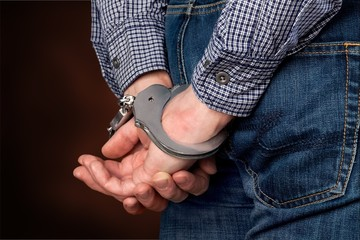 Cropped image of male hands in handcuffs
