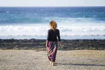 beautiful lonely caucasian middle age woman walk and enjoy the nobody beach in season. freedom and alternative lifestyle concept for independence lady feeling the ocean and nature