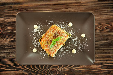 Lasagna with spinach on wooden background