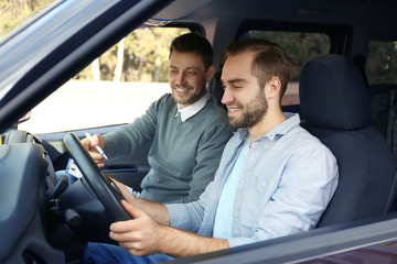 Young man and driving instructor in car