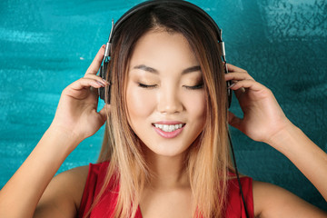 Portrait of happy Asian woman listening to music against color background