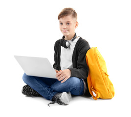 Teenager studying with laptop on white background